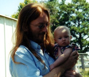 Corey several years back in John Lennon mode, holding my great-niece Abrie.