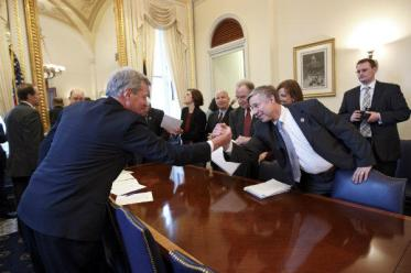 Something that doesn't happen enough: compromise. Sen. Max Baucus (D) of Montana, left, reaches across the table to shake hands with Rep. Fred Upton (R) of Michigan after bipartisan House and Senate conferees signed a compromise agreement on the payroll tax cut extension. Image by  J. Scott Applewhite/AP.