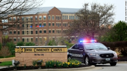 A police car sits at the entrance of the Jewish Community Campus, the scene of two of three shooting deaths Sunday in Overland Park, Kan. Image from CNN.