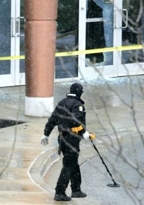 A crime scene investigator uses a metal detector Sunday at the shooting scene at the Jewish Community Campus in Overland Park, Kan. Image by Fred Blocher, Kansas City Star.