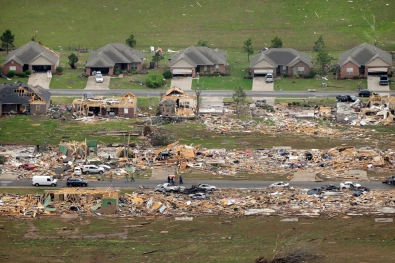 A row of lightly damages houses, top, face destroyed homes in a Vilonia neighborhood after a tornado struck the town late Sunday. Image by Danny Johnston/AP.