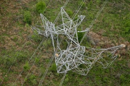 A twisted power distribution line tower is crumpled on the ground near Mayflower after a tornado struck the town late Sunday. (Danny Johnston/AP