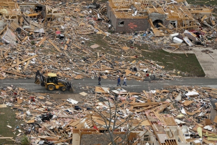 People walk between two destroyed houses in Mayflower on Monday. Image by Danny Johnston/AP.