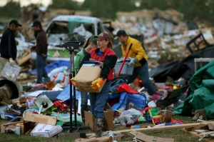 Volunteer Gina Lowe helps a family move belongings from a home that was destroyed by a tornado two days before in Vilonia. Mark Wilson/Getty Images.