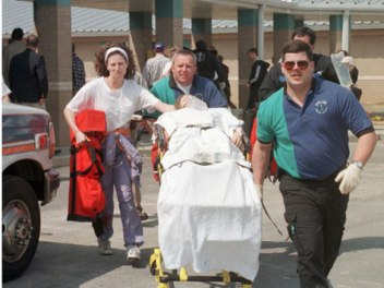 Emergency workers move one of the wounded in the Westside shooting to an ambulance. Shannon Wright, Paige Herring, Stephanie Johnson, Brittheny Varner and Natalie Brooks died in the attack. Image by Curt Hodges, Jonesboro Sun.