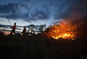 People tend a fire to clear debris in Vilonia. Image by Carlo Allegri, Reuters.
