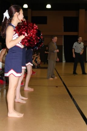 Providence Academy coach Austin Bivens coaches a basketball game in bare feet for the Samaritan's Feet organization. Cheerleaders for the Rogers school also went barefoot. Image from NWA Media.