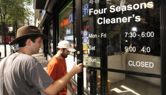 Jeff Deck holds the door for Benjamin Herson as they enter a dry cleaning establishment in Philadelphia to ask if they can remove the errant apostrophe in the name. Image by MCT,