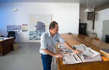 Editor Robert Halpern at the layout desk of the Big Bend Sentinel in Marfa, Texas. Charming, but not so busy there, like most small papers. Image by Joshua Bright of Town & Country Magazine.