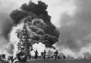 Flames leap from the deck of the USS Bunker Hill, after it was hit by two Kamikazes in 30 seconds on May 11, 1945 off Kyushu. 346 aboard were killed, another 264 wounded. (U.S. Navy) Image found on The Atlantic.