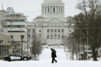 A woman walks across Capitol Avenue in Little Rock on Monday. Image by Associated Press.